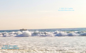 Photograph of a boat riding the waves in soft light by M. Caulder.